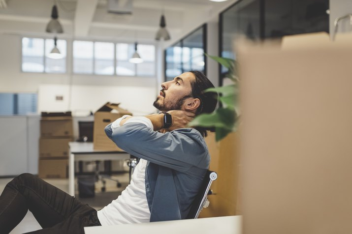Side view of young businessman having neck ache while sitting in new office