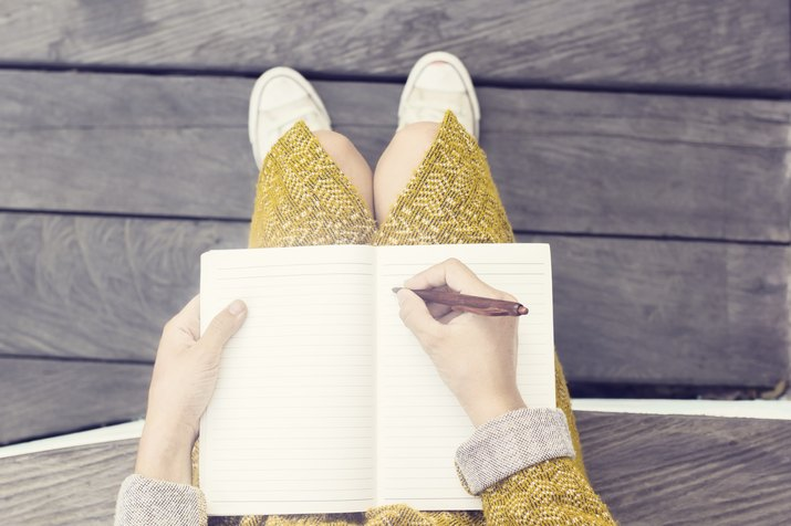 Woman writing in a blank journal