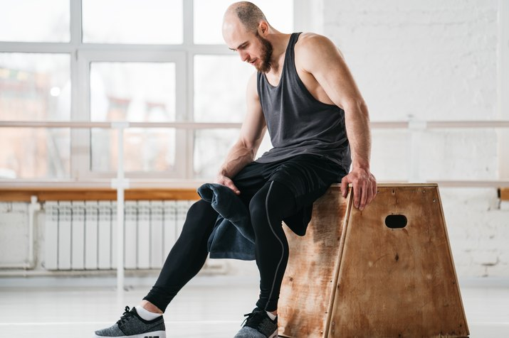 Sweaty muscular man sitting on box in gym gym. Strong male athlete resting after hard workout in light hall