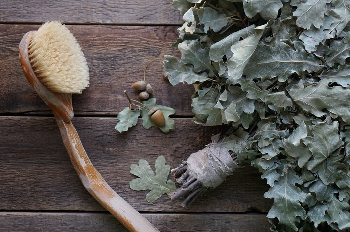 Close view of a bristle brush and herbs on a wooden background
