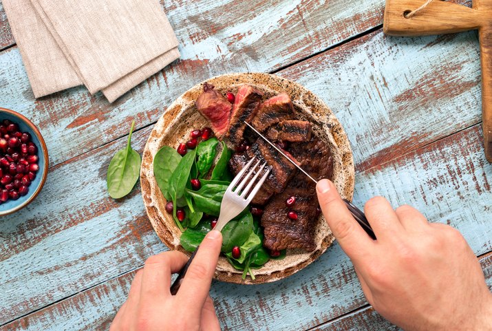 Man eats a beef grilled steak on wooden table. Rustic style