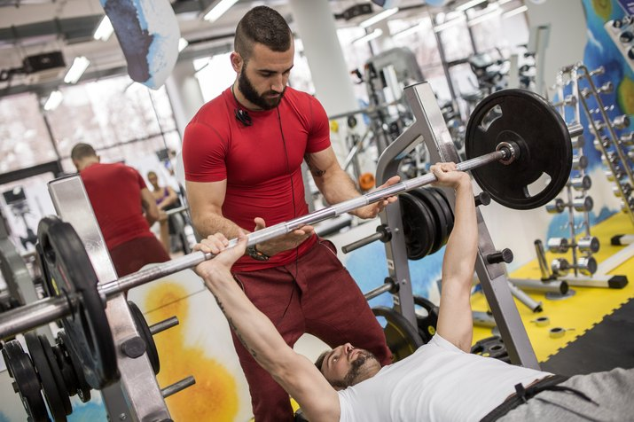 Weightlifting training with fitness instructor in a gym