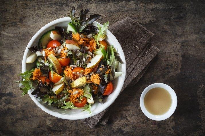 Fresh mixed salad with kohlrabi, tomato and cucumber on wood