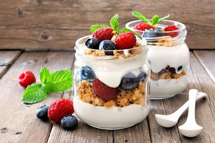 Blueberry, raspberry parfaits with yogurt in mason jars, still life against wood