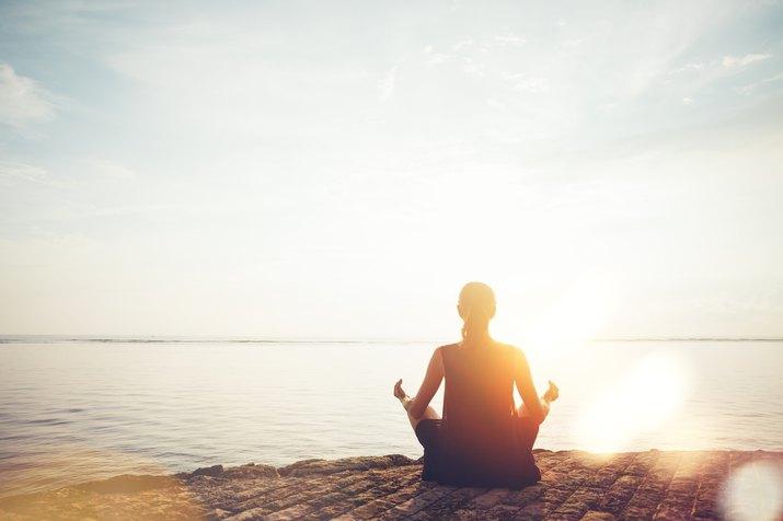Woman on beach practicing yoga