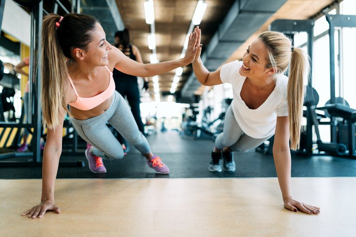 Two attractive fitness girls doing push ups