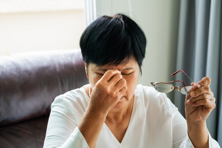 Woman removing eyeglasses, massaging eyes after reading paper book. feeling discomfort because of long wearing glasses, suffering from dizziness