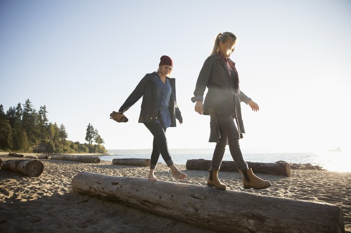 Mother and daughter walking, balancing on log on sunny ocean beach