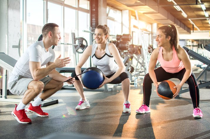 Two sporty women doing exercises with fitness balls with assistance of their personal trainer in gym.
