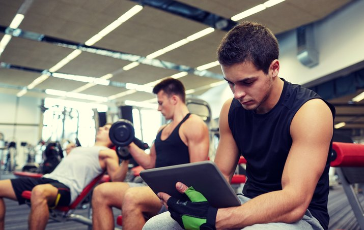 group of men with tablet pc and dumbbells in gym