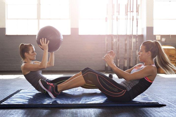 Women doing abdominal exercise using ball