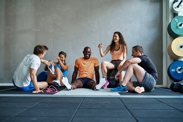 Diverse group of friends sitting together in a gym laughing