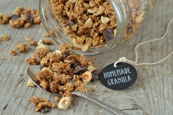 Close-Up Of Homemade Granola By Glass Jar And Tag With Text On Wooden Table