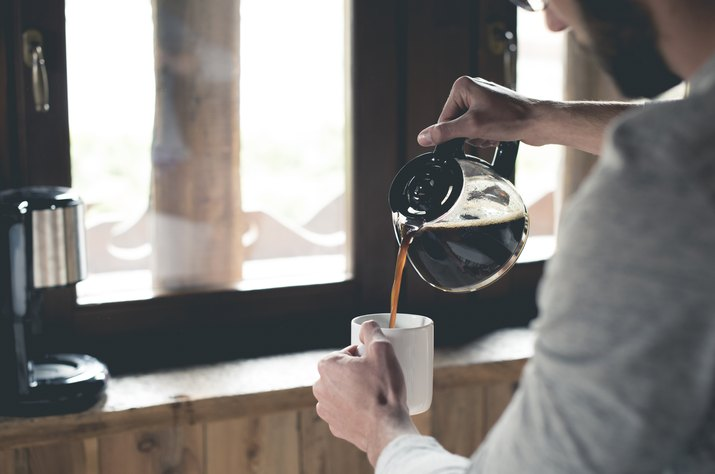 Young man pouring coffee into cup at home