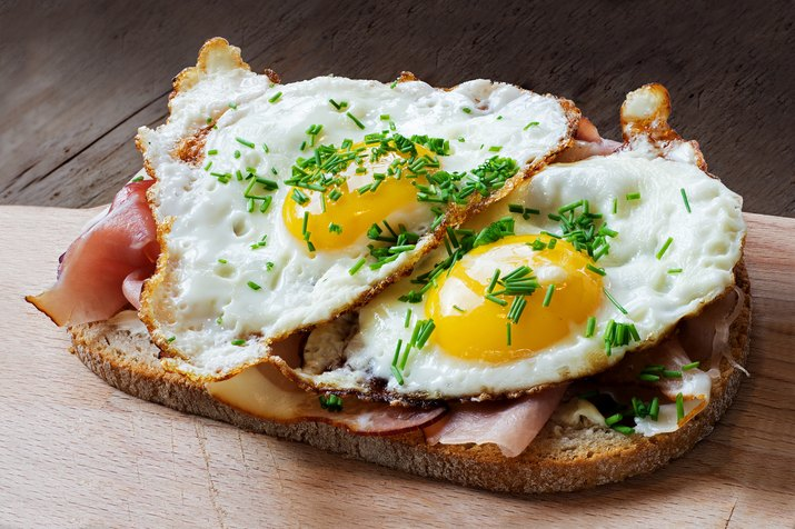 Slice of rustic bread with ham  and fried eggs