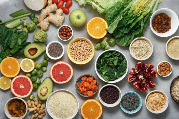 Set clean eating. Vegetarian healthy food - different vegetables and fruits, superfood, seeds, cereal, leaf vegetable on light background, top view. Flat lay