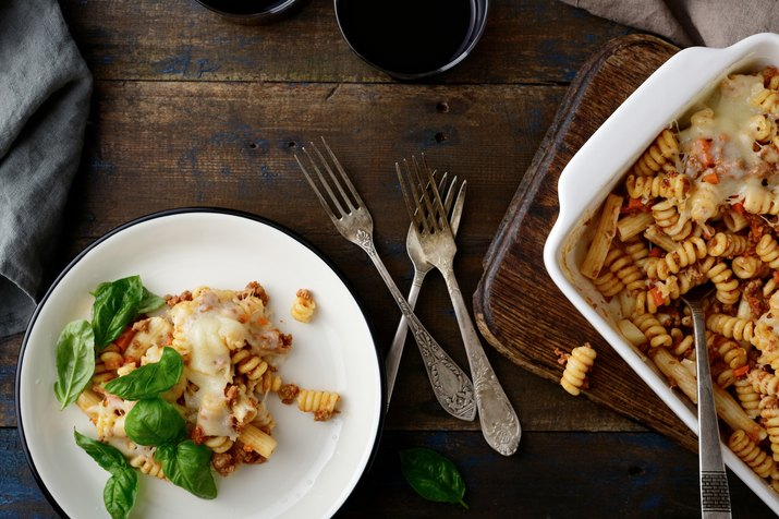 Pasta Bolognese with basil on plate and in baking dish