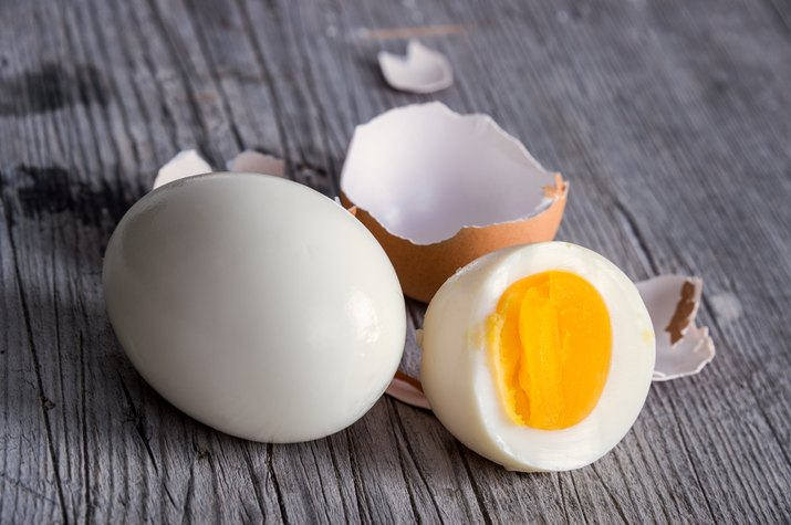 Sliced hard boiled eggs on wooden cutting board