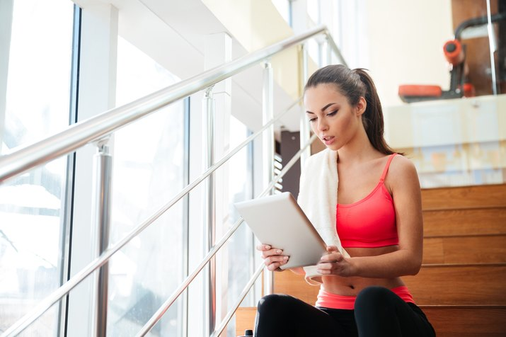 Thougtful sportswoman using tablet after training in gym