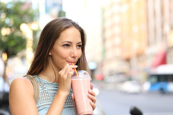 Woman eating a milkshake in the street
