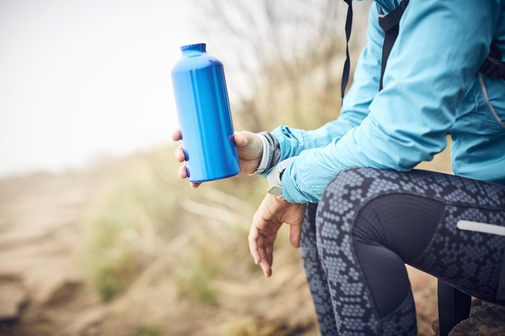 Midsection of woman hiker drinking from a water bottle