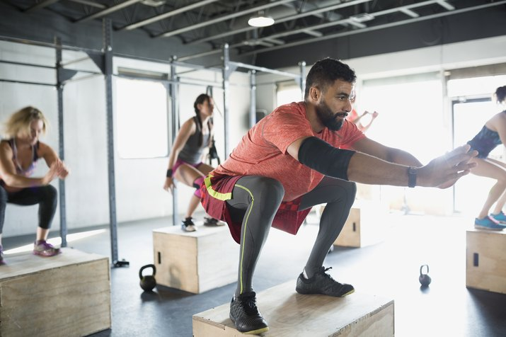 Focused man jump squats in gym exercise class