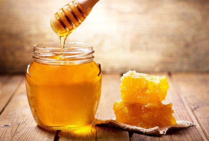 pouring honey into jar of honey