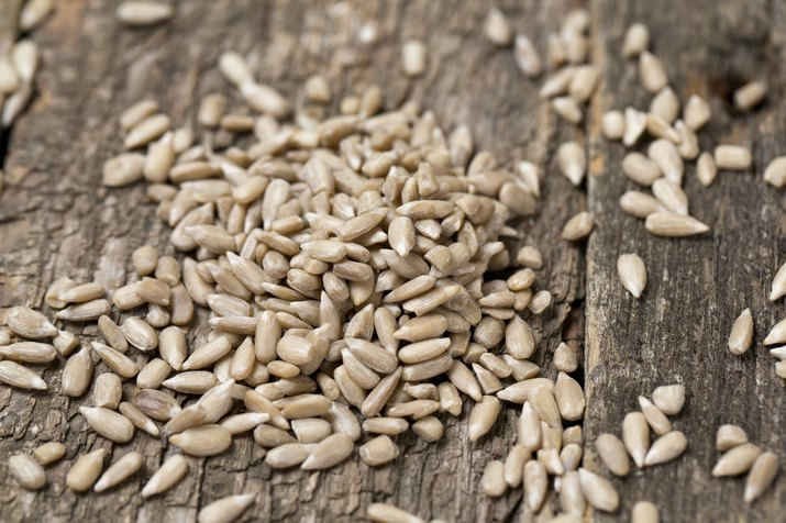peeled sunflower seeds on wooden surface