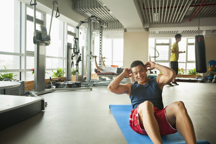 Young man doing sit-ups in the gym