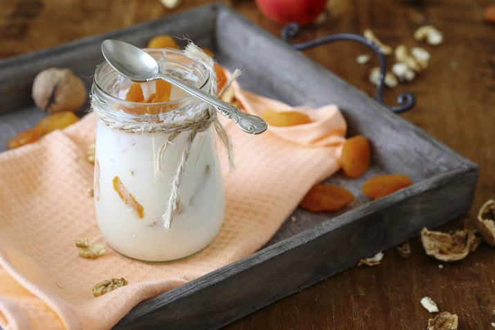 jar fresh yogurt with nuts and apricots on  old tray