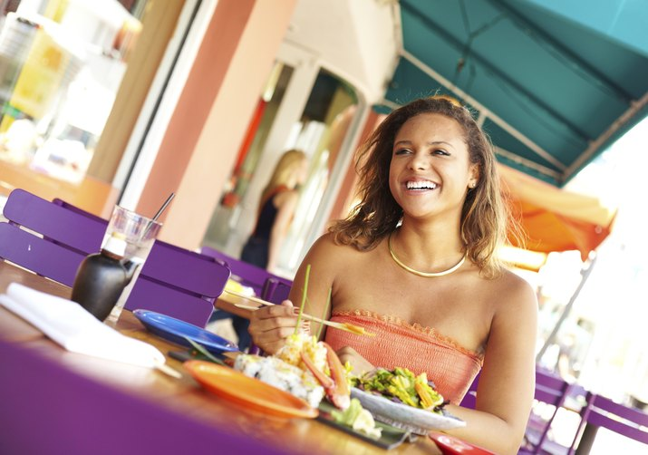 Pretty Mixed Race Woman Enjoying Meal At A Restaurant