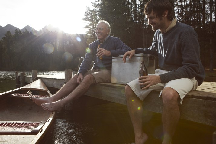 Father and son having a beer on jetty