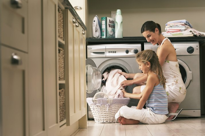 Girl (7-9) helping mother with laundry, smiling