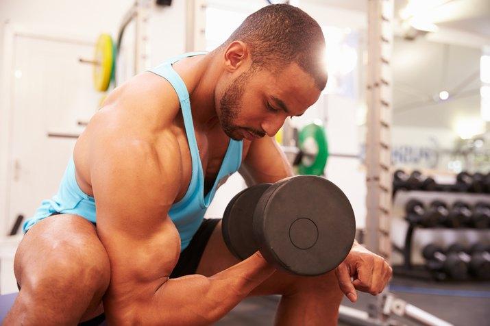 Man exercising with dumbbells at a gym, horizontal shot