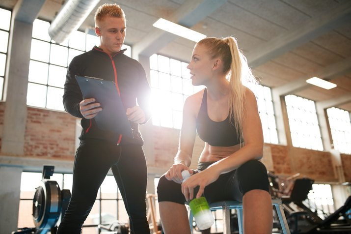 Young woman discussing exercise plan with her personal trainer