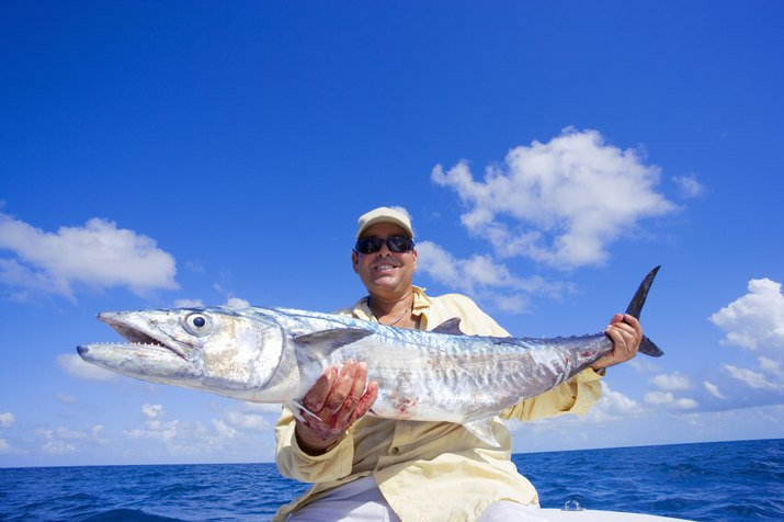Man posing with freshly caught king mackerel, portrait