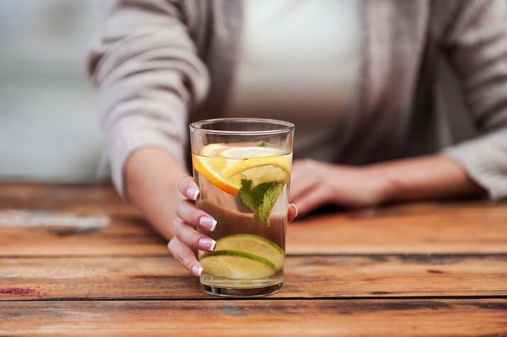 A woman drinking a glass of water with lemon and lime slices