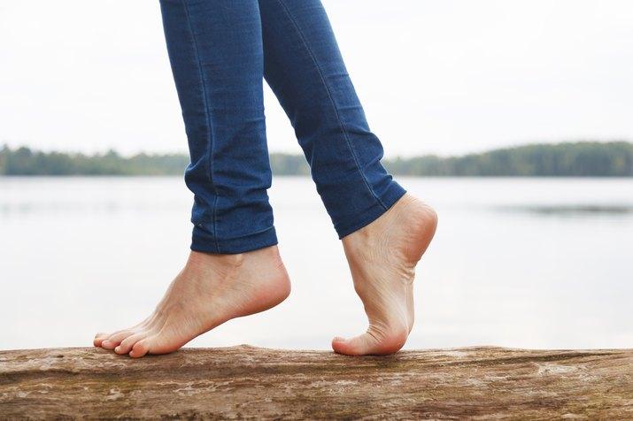 A woman's bare feet walking on a log near a lake