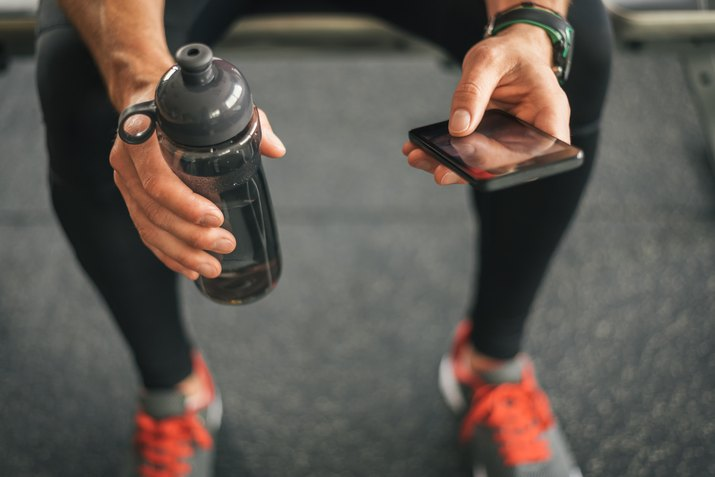 Fitness man looking to the phone for motivation before workout