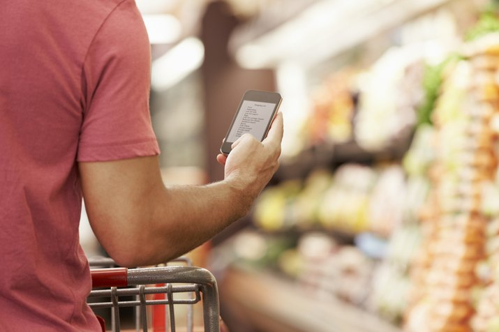 Man with shopping cart reads from cell phone