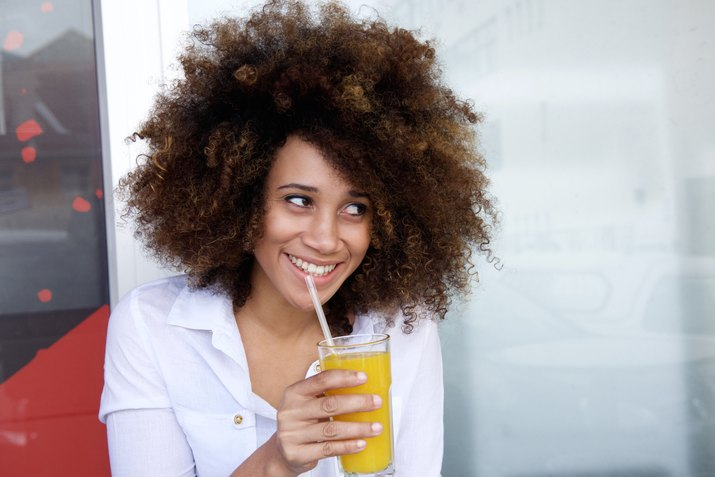 Smiling young african woman drinking juice at outdoor cafe