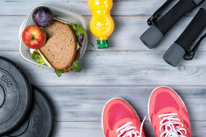 Fitness concept, pink sneakers, weight plates, dumbbells, sandwich
