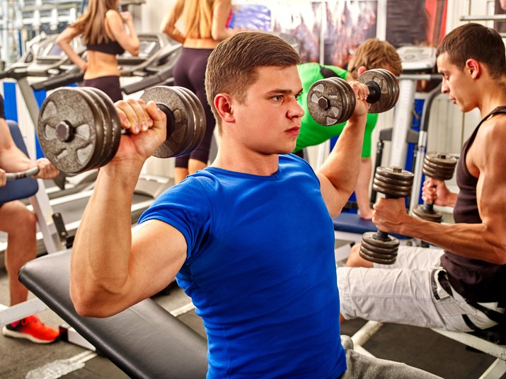 Group of men working with dumbbells  at gym