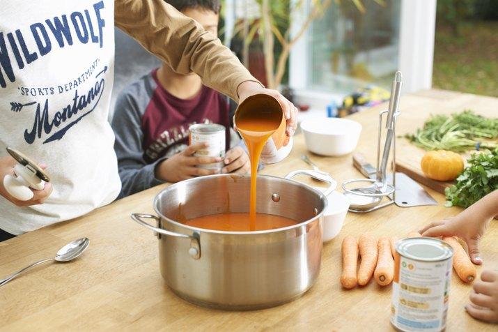 Cropped shot of boy pouring tin of tomato soup into saucepan
