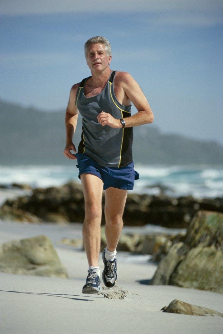 Mature man jogging on rocky beach