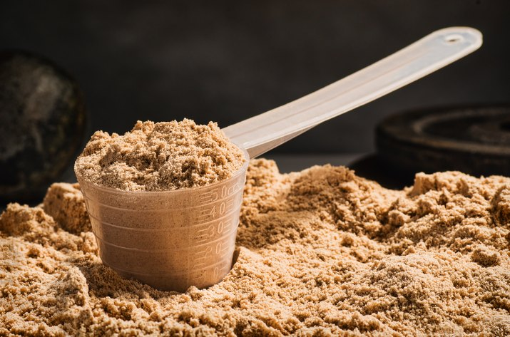 Scoop of whey protein on black background for muscle building diet