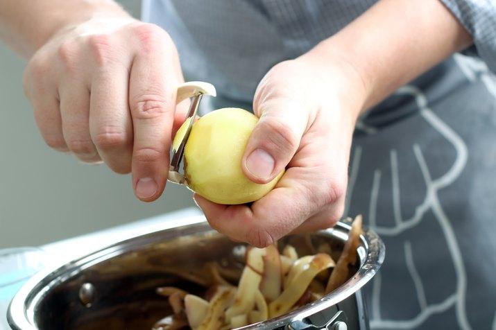 Man peeling  potatoes. Kitchen working. Prepare food