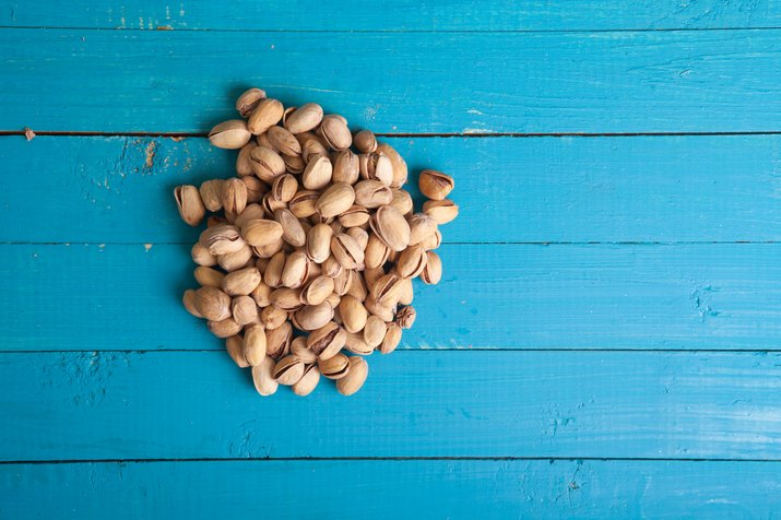 salted pistachios on a blue wooden table