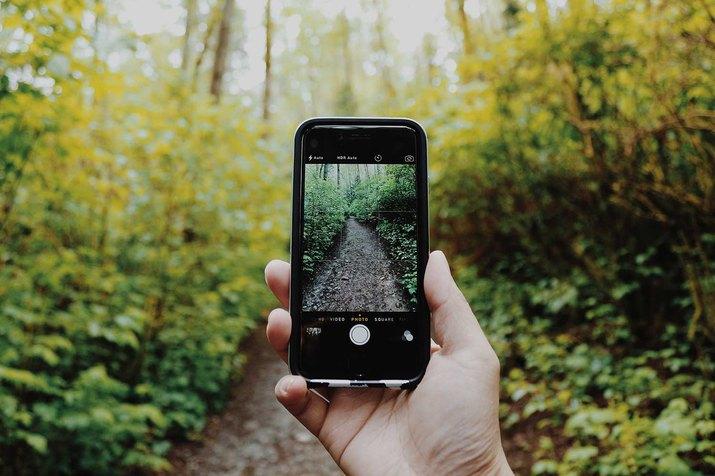 Man taking photo of landscape to improve exercise accountability.