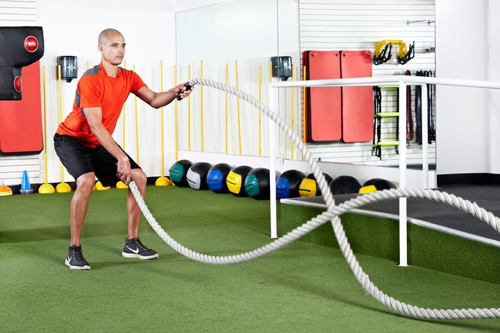 Man doing standing squats with alternating waves with the battle ropes